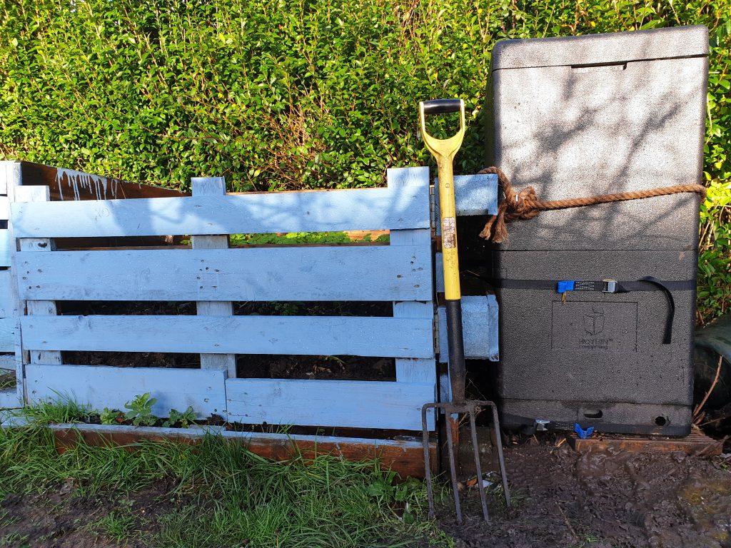 An insulated compost bin next to a pallet bin.