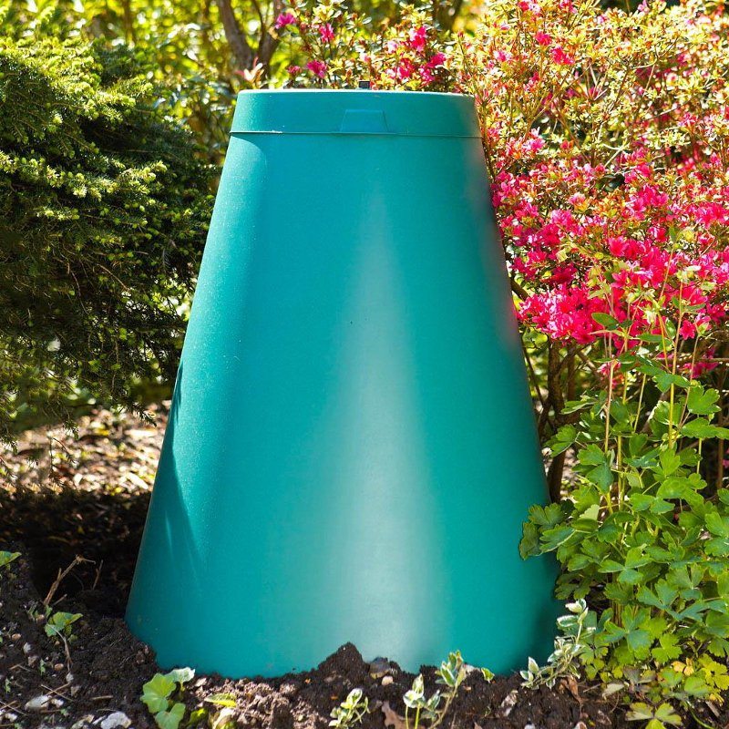 Green Cone digester against a background of flowers.